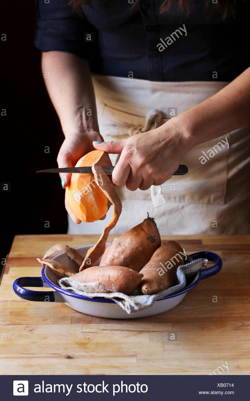 Peeling hembra naranja batatas. Imagen De Stock