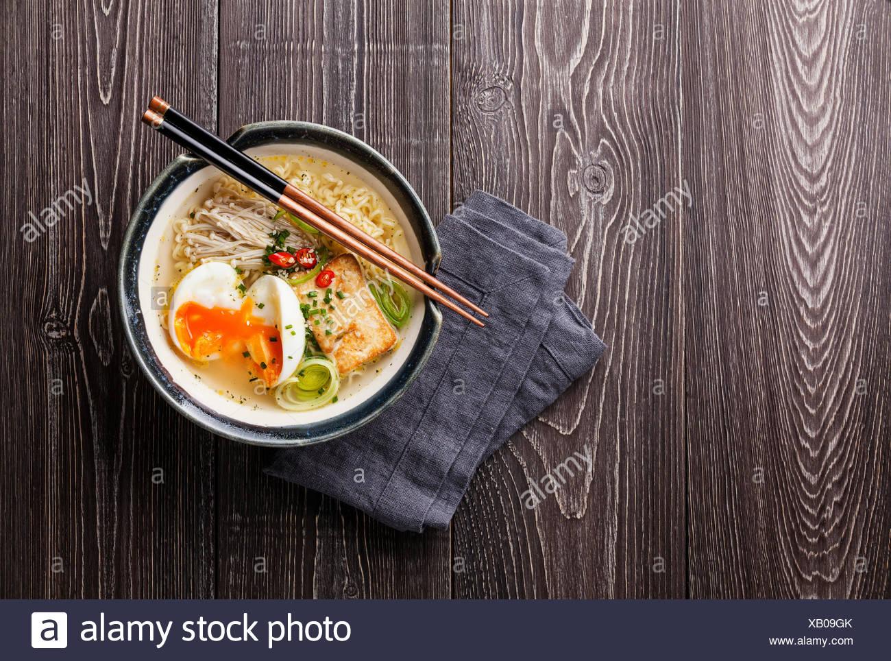 Fideos asiáticos con huevo, tofu y enoki en tazón en gris de fondo de madera Imagen De Stock