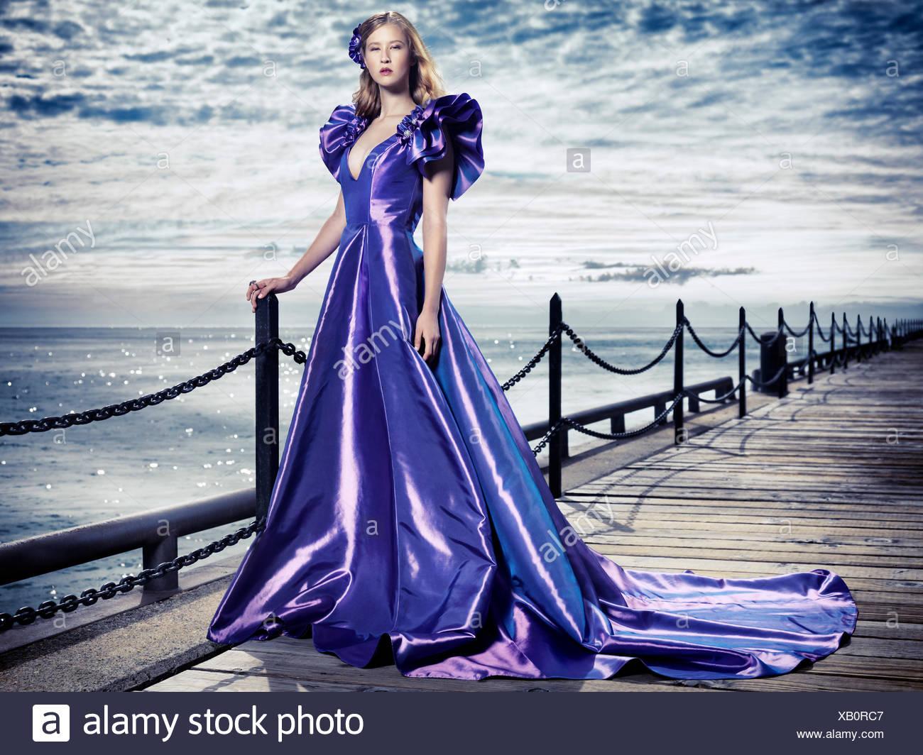 Mujer joven llevando un vestido de noche, en la costanera, retrato de moda Imagen De Stock