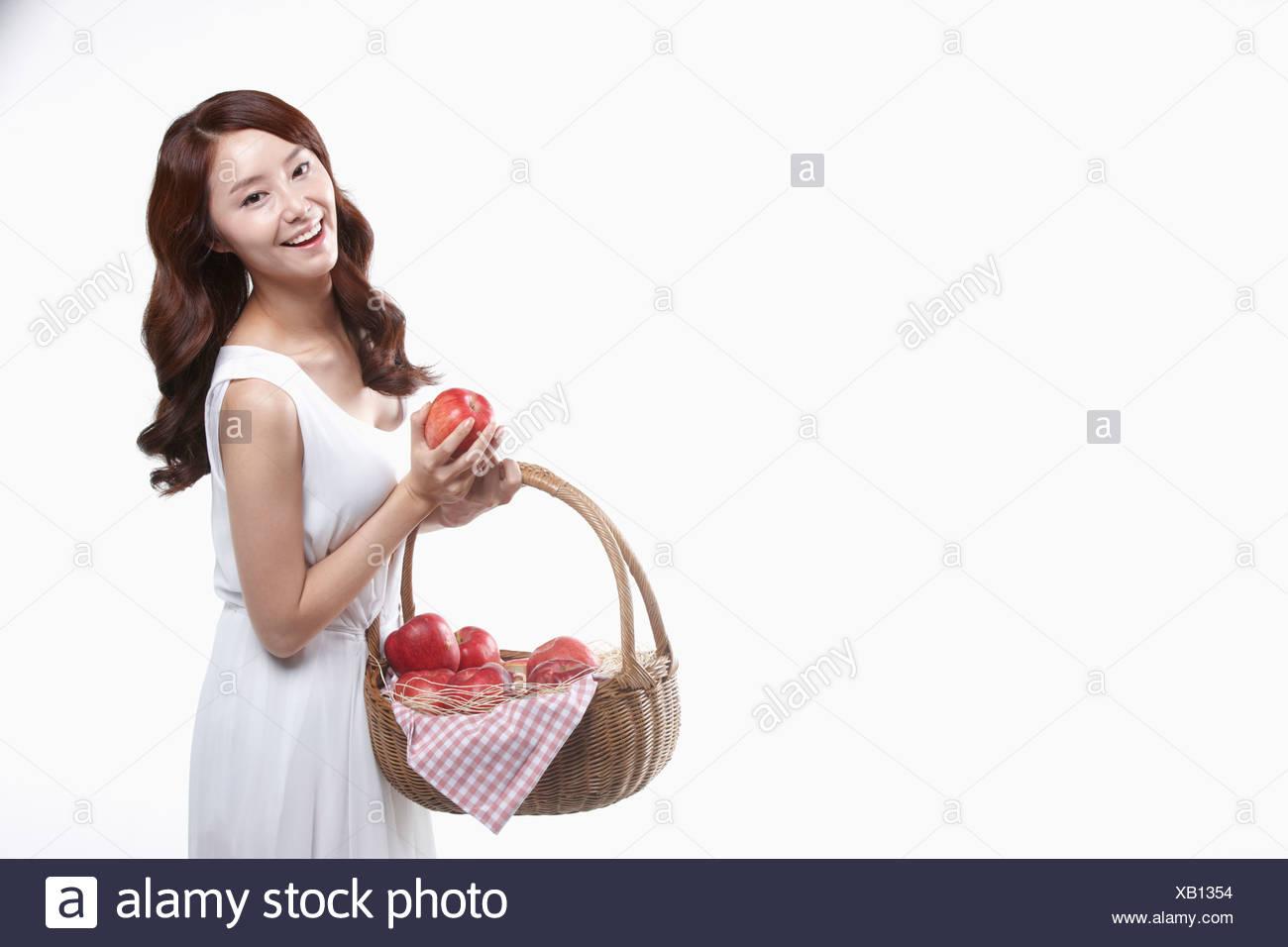 Una señora en vestido blanco sosteniendo una cesta de manzanas. Imagen De Stock