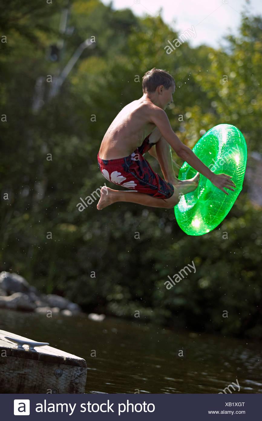 Muchacho saltando de base y en el lago. Foto de stock