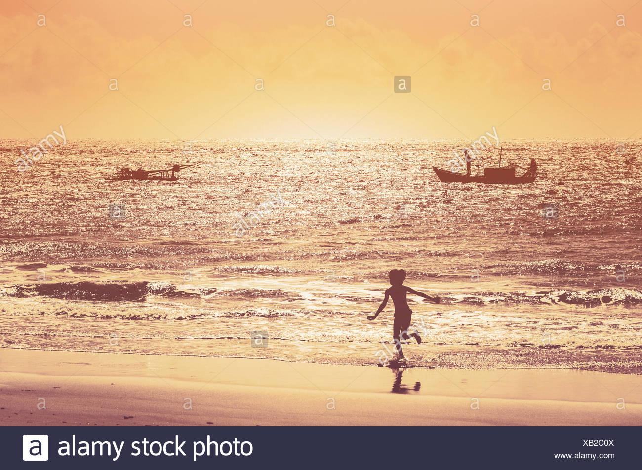 Brasil, Pirangi, Rio Grande do Norte, niña corriendo por la playa al atardecer. Imagen De Stock