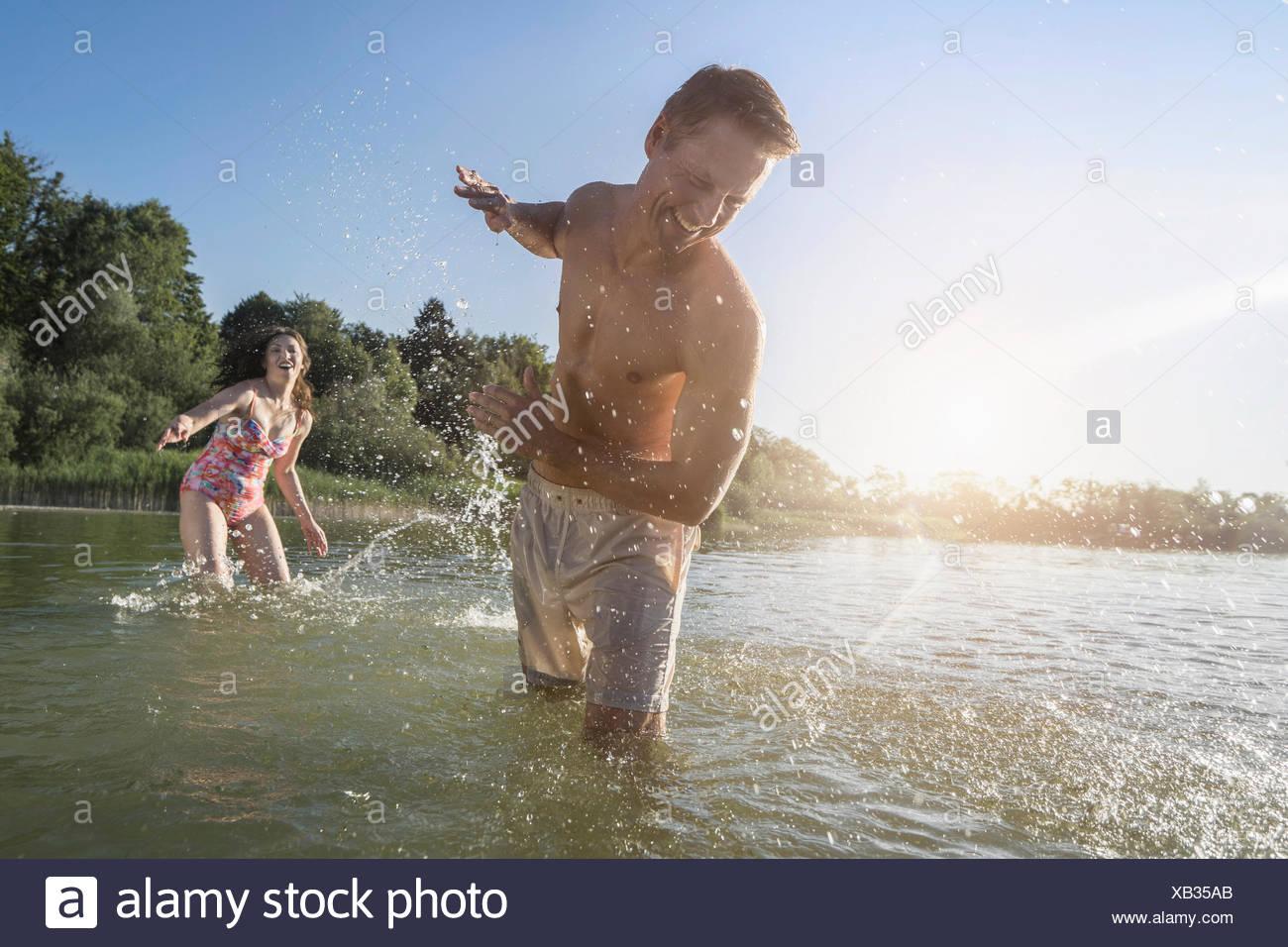 Mujer madura, salpicaduras de agua sobre su marido en el lago, Baviera, Alemania Imagen De Stock