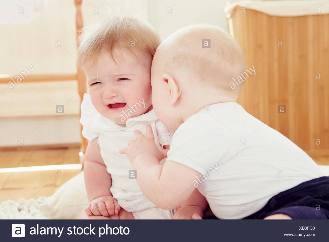 El llanto del bebé niña con baby boy inclinándose hacia ella Imagen De Stock
