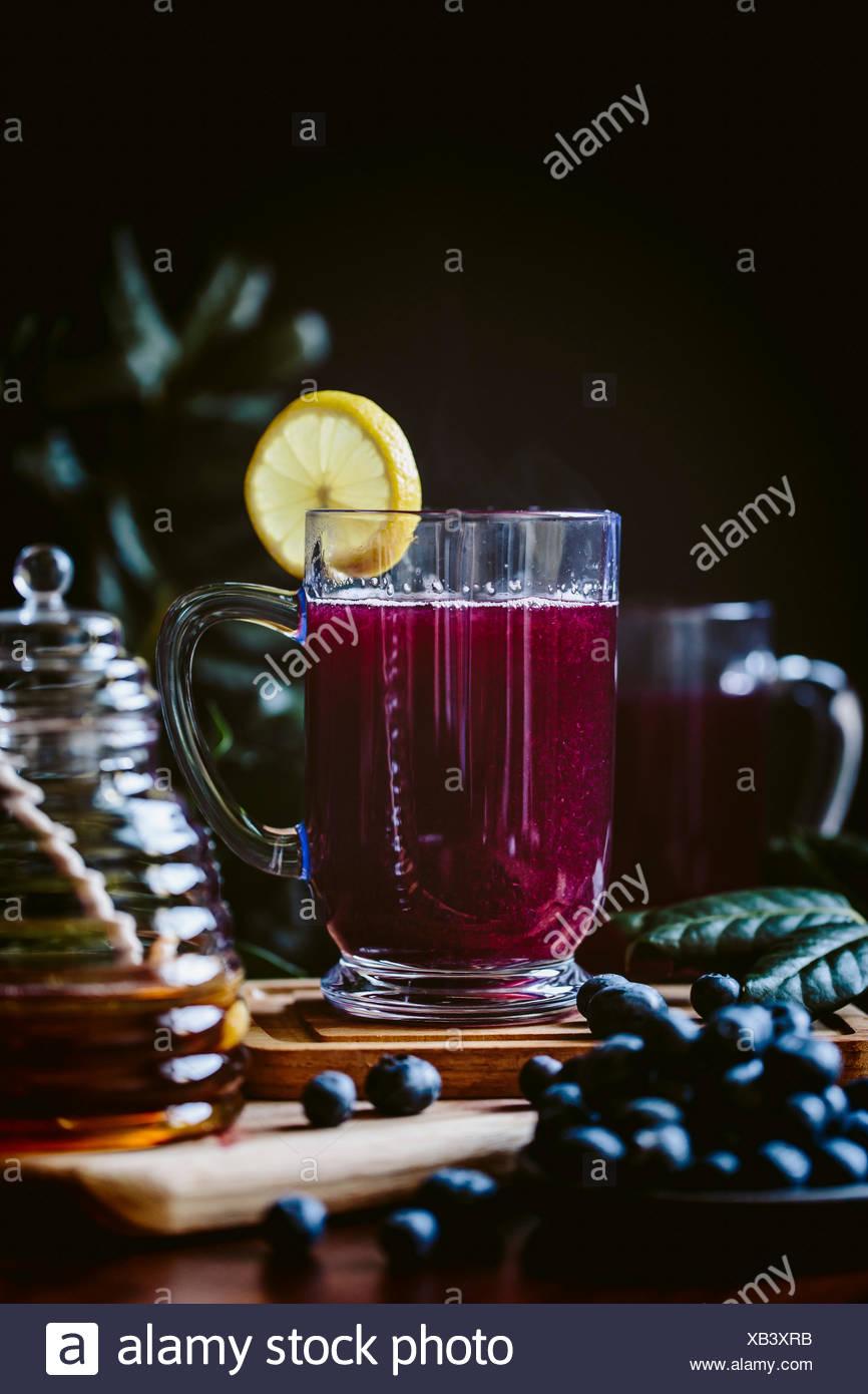 Un vaso de arándano toddy caliente aderezado con una rodaja de limón es fotografiado desde la vista frontal. Foto de stock
