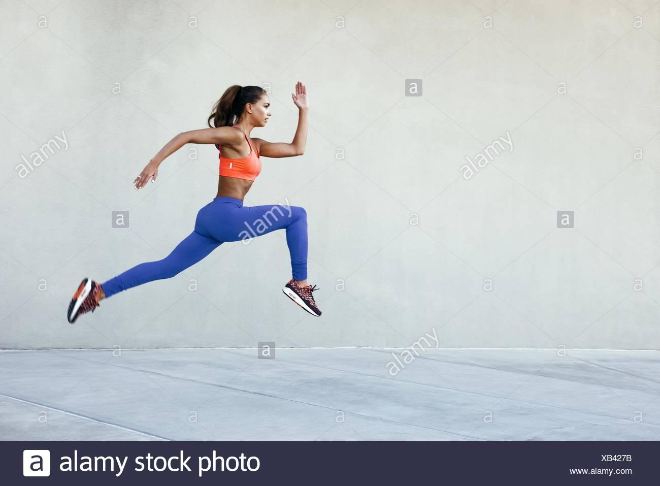Vista lateral de la joven mujer vistiendo ropa deportiva en medio del aire que inician postura Imagen De Stock