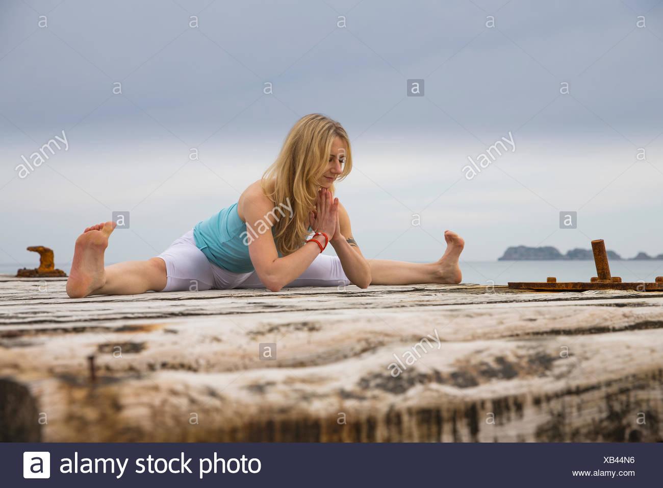 Mitad mujer adulta con manos juntas practicando yoga en Mar del muelle de madera Foto de stock