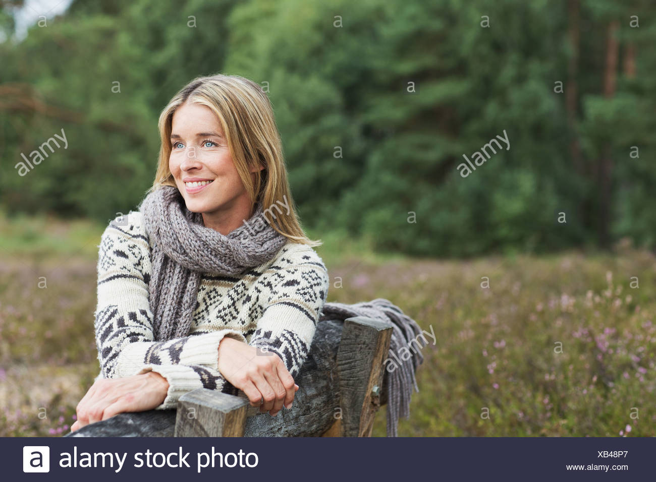 Mujer adulta media vistiendo suéter en un banco Foto de stock