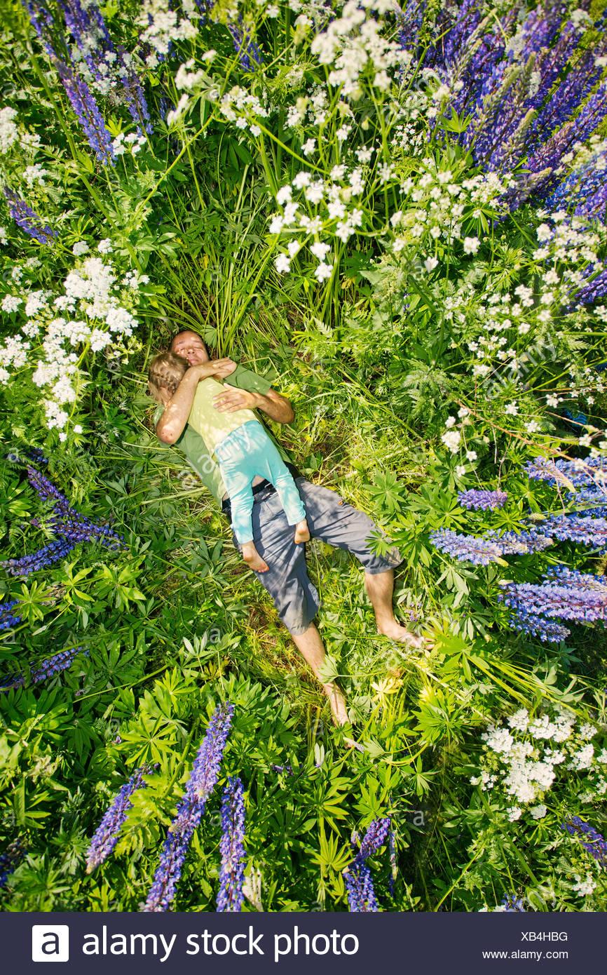 Finlandia, el hombre y la chica (2-3) tumbado en la pradera Imagen De Stock