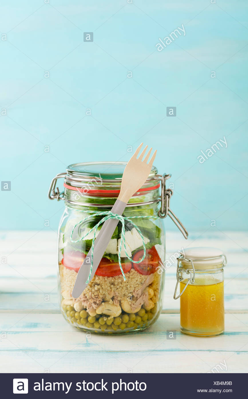 Salat zum Mitnehmen Glas im mit Erbsen, Cashew-Nüssen, Thunfisch, cuscús, Cocktailtomaten, Minze, Schafskäse, Blattsalat und vinagreta Foto de stock