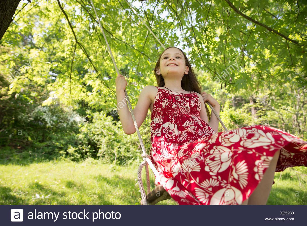 En el verano. Una niña de un sundress en un columpio de suspender desde las ramas de un árbol. Imagen De Stock