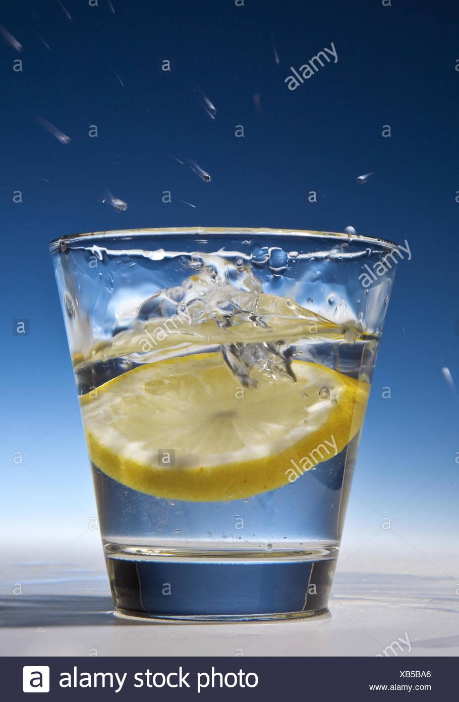 Rodaja de limón cayendo en un vaso con agua Imagen De Stock