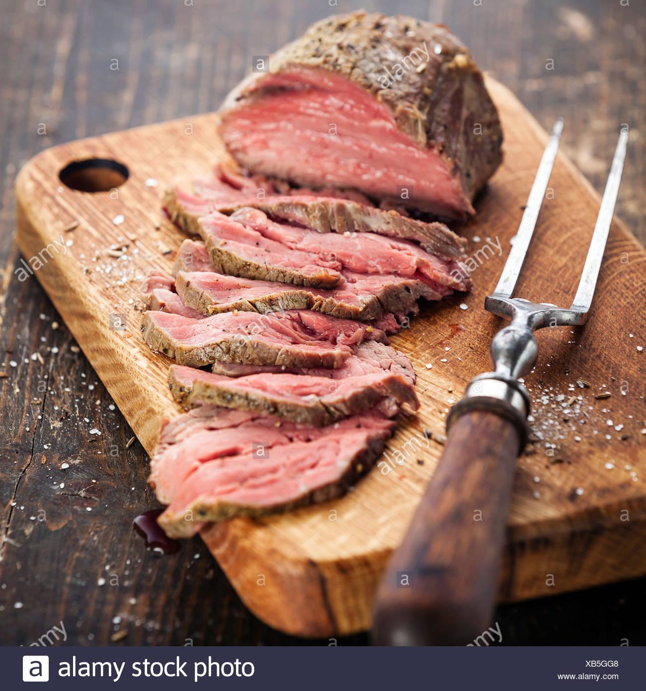 Carne asada en la tabla de cortar carne y horquilla Imagen De Stock