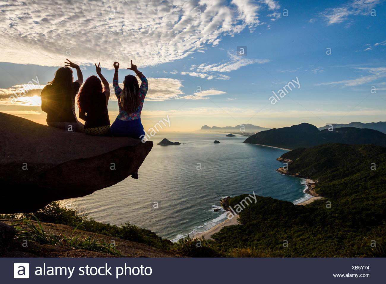 La mujer en el borde de la montaña en Pedra do Telégrafo deletrear el amor con sus dedos, Río de Janeiro, Brasil Imagen De Stock