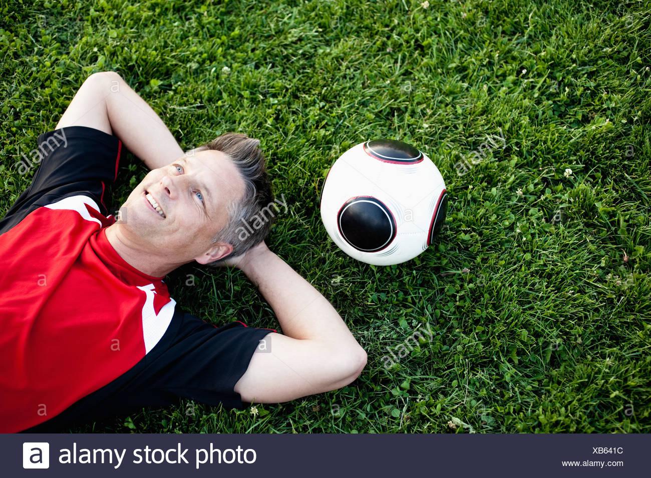 Jugador de fútbol sobre hierba relajante Foto de stock