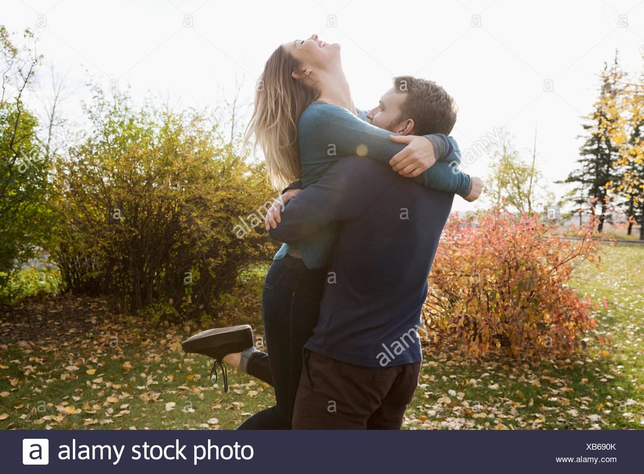 Pareja juguetona riendo y abrazando en otoño park Imagen De Stock