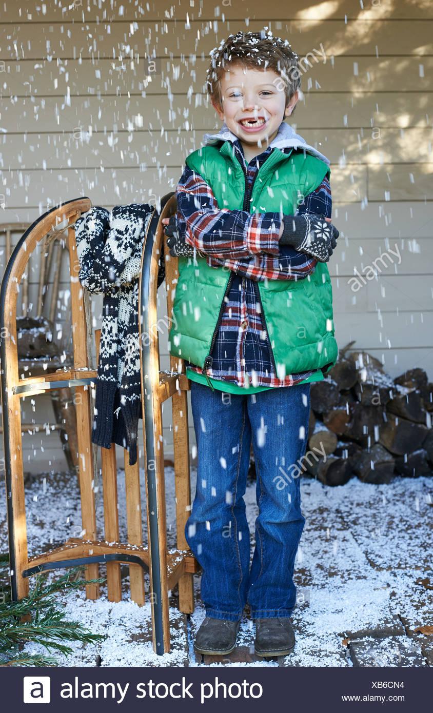 Niño con trineo de madera en la nieve Imagen De Stock