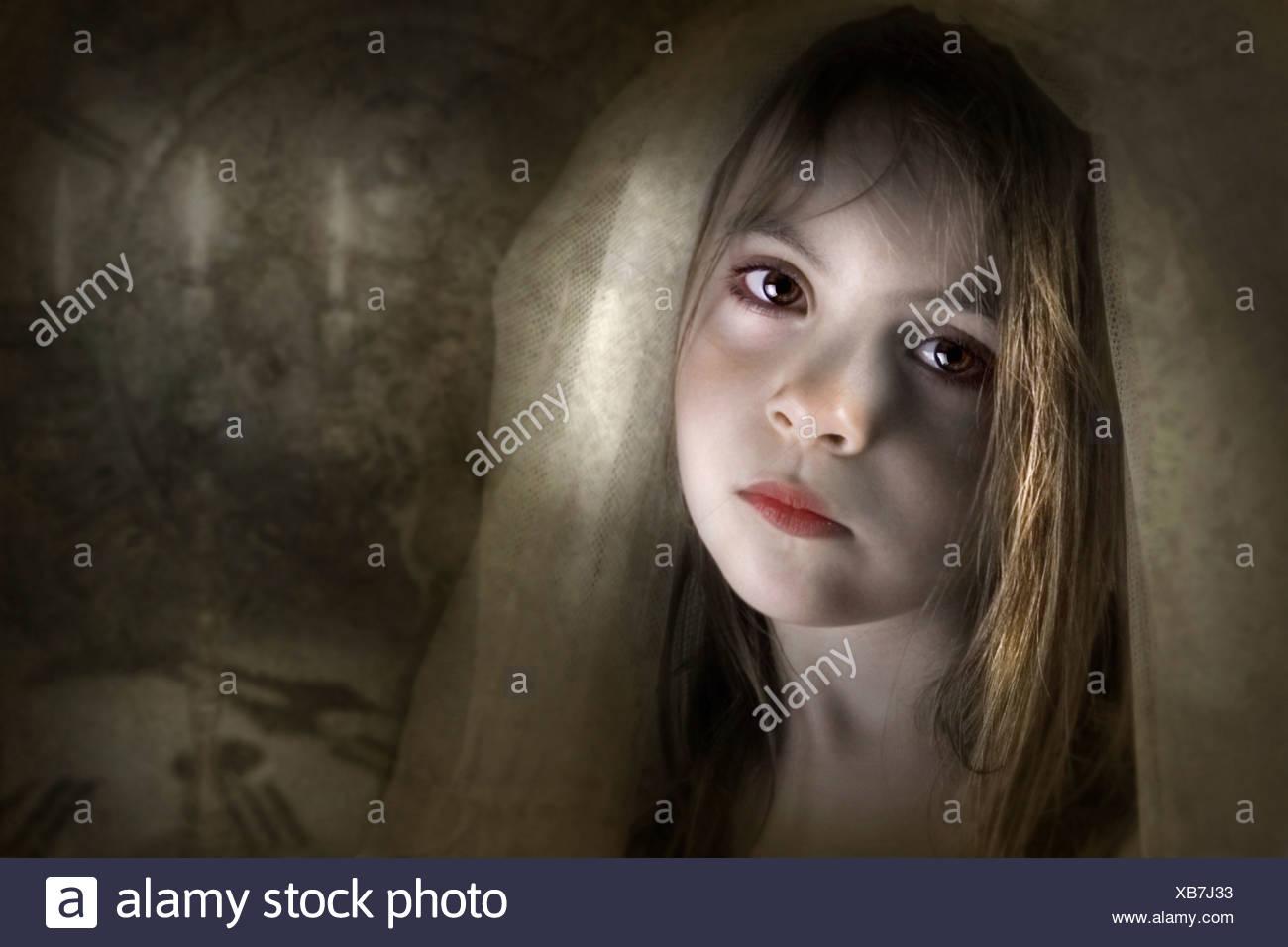 Niño joven vestida con un velo mirando a la cámara con tristeza o dolor en un establecimiento de ambiente Imagen De Stock