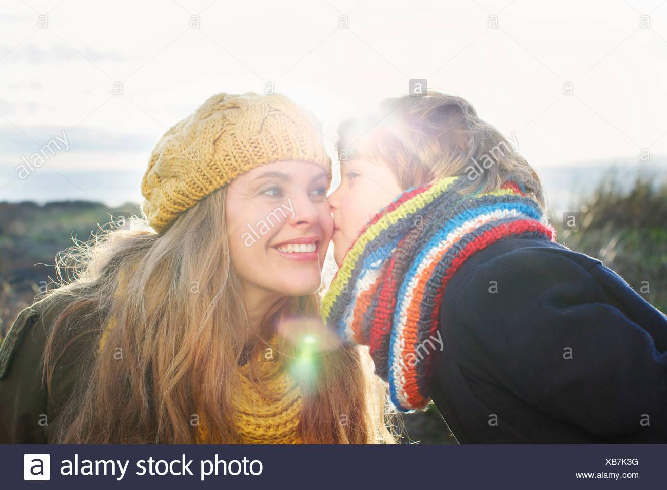 Mitad mujer adulta con hijo besar su mejilla en la costa Imagen De Stock