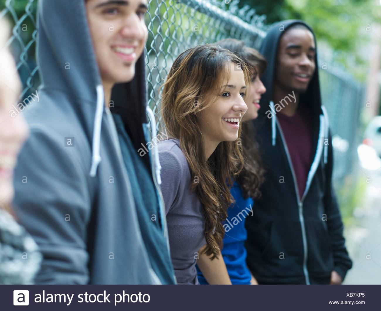 Cinco adolescentes apoyándose contra el eslabón de la cadena cerco Imagen De Stock