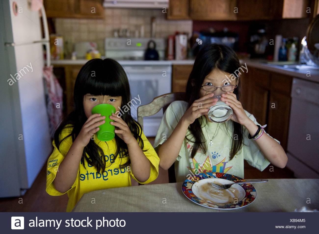 Dos niñas beber su leche antes de ir a la escuela. Imagen De Stock