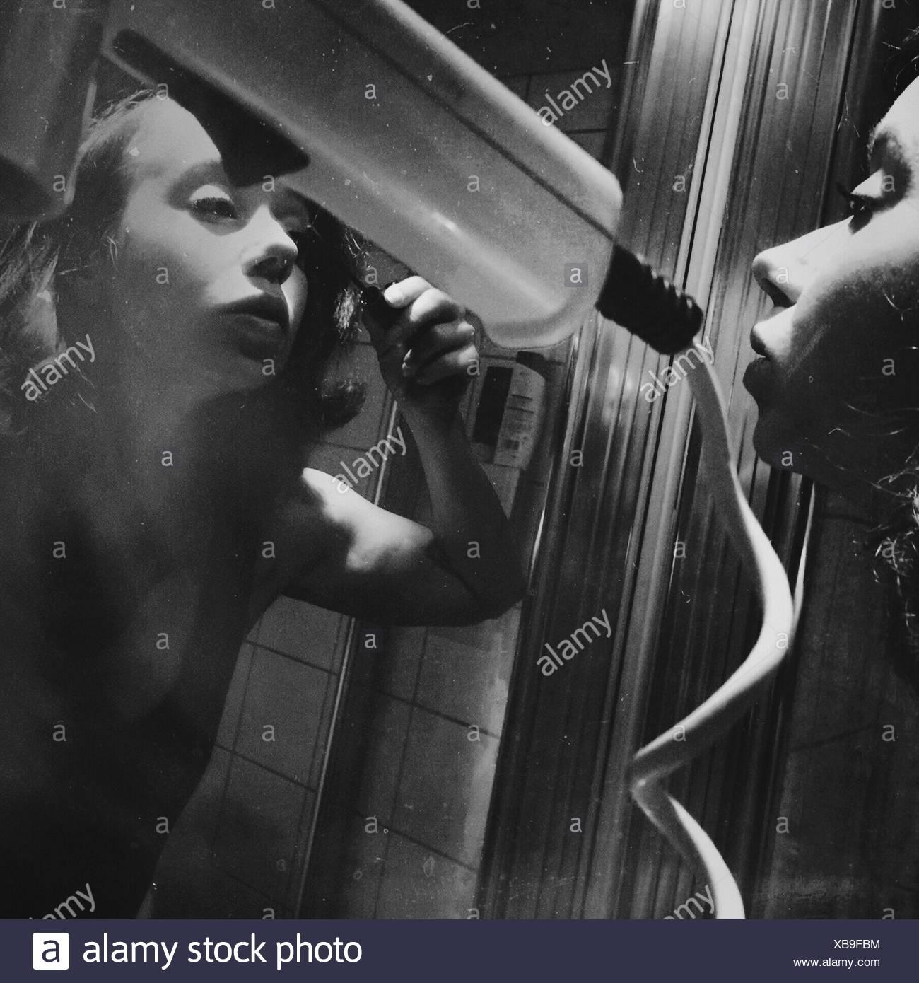 Mujer joven de aplicar el rímel mientras se mira en el espejo Imagen De Stock