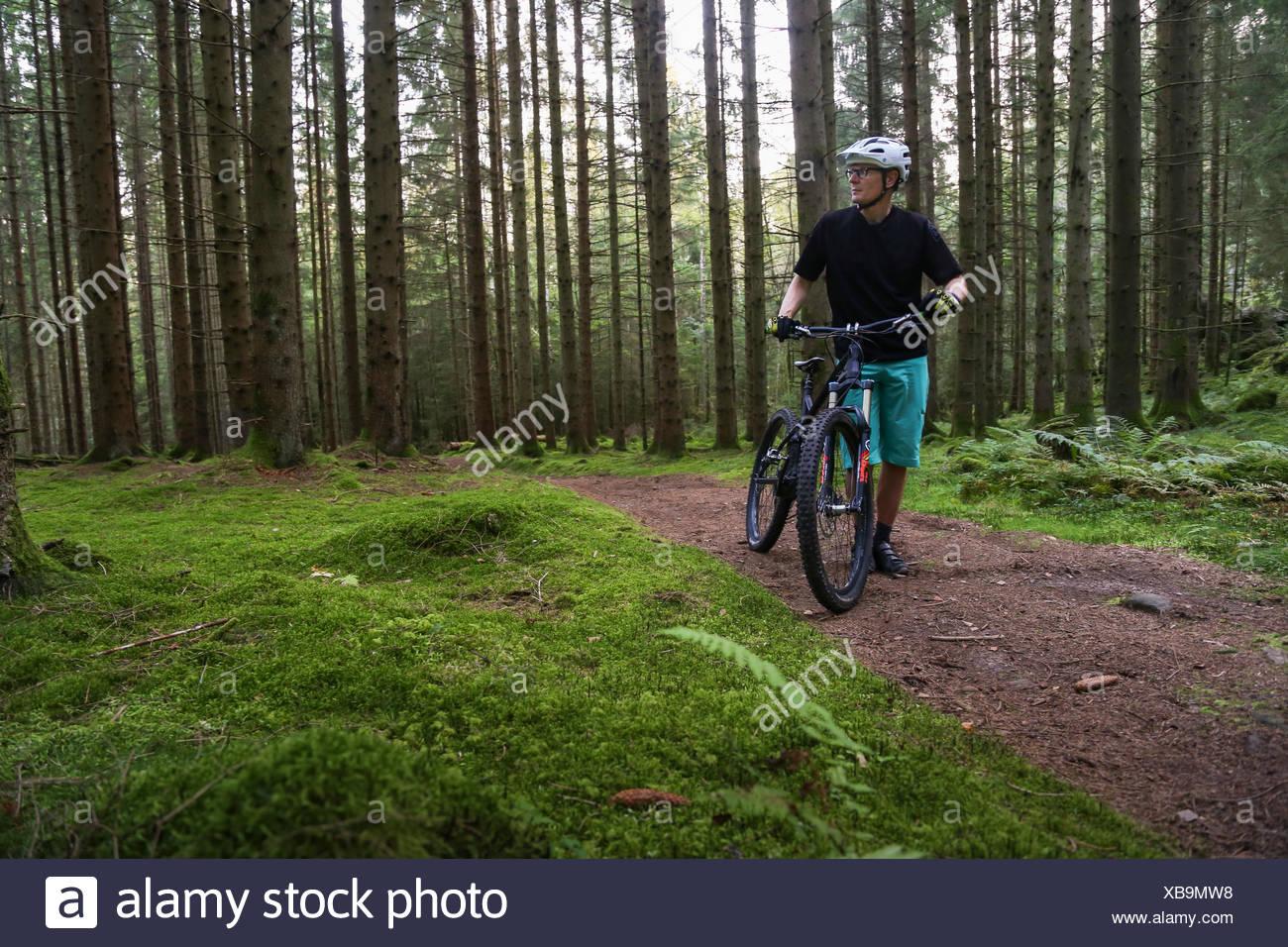 Suecia, Vastergotland, Lerum, hombre maduro con bicicleta en el bosque Foto de stock