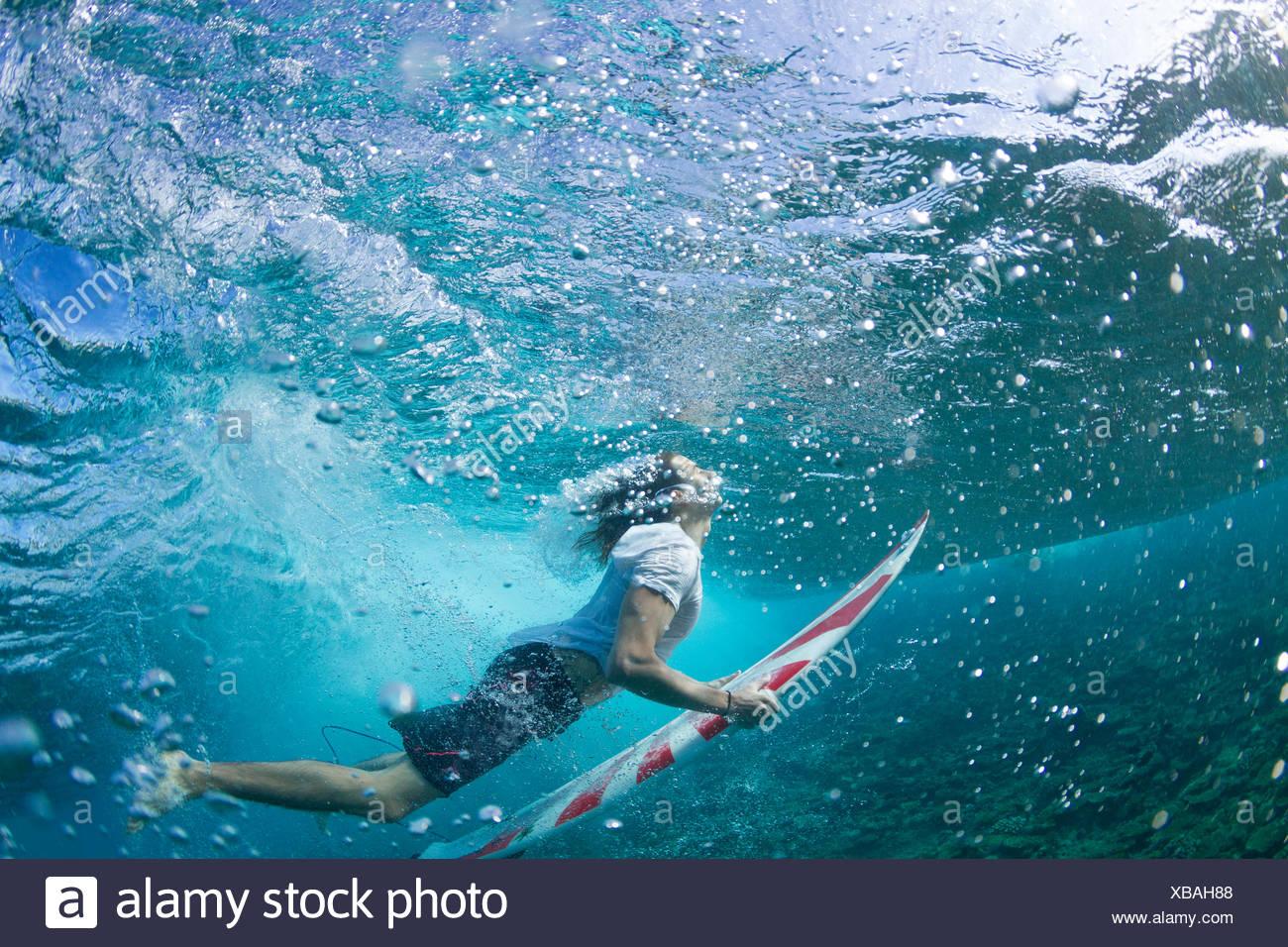 Vista submarina de un surfista pato de buceo bajo una ola Imagen De Stock