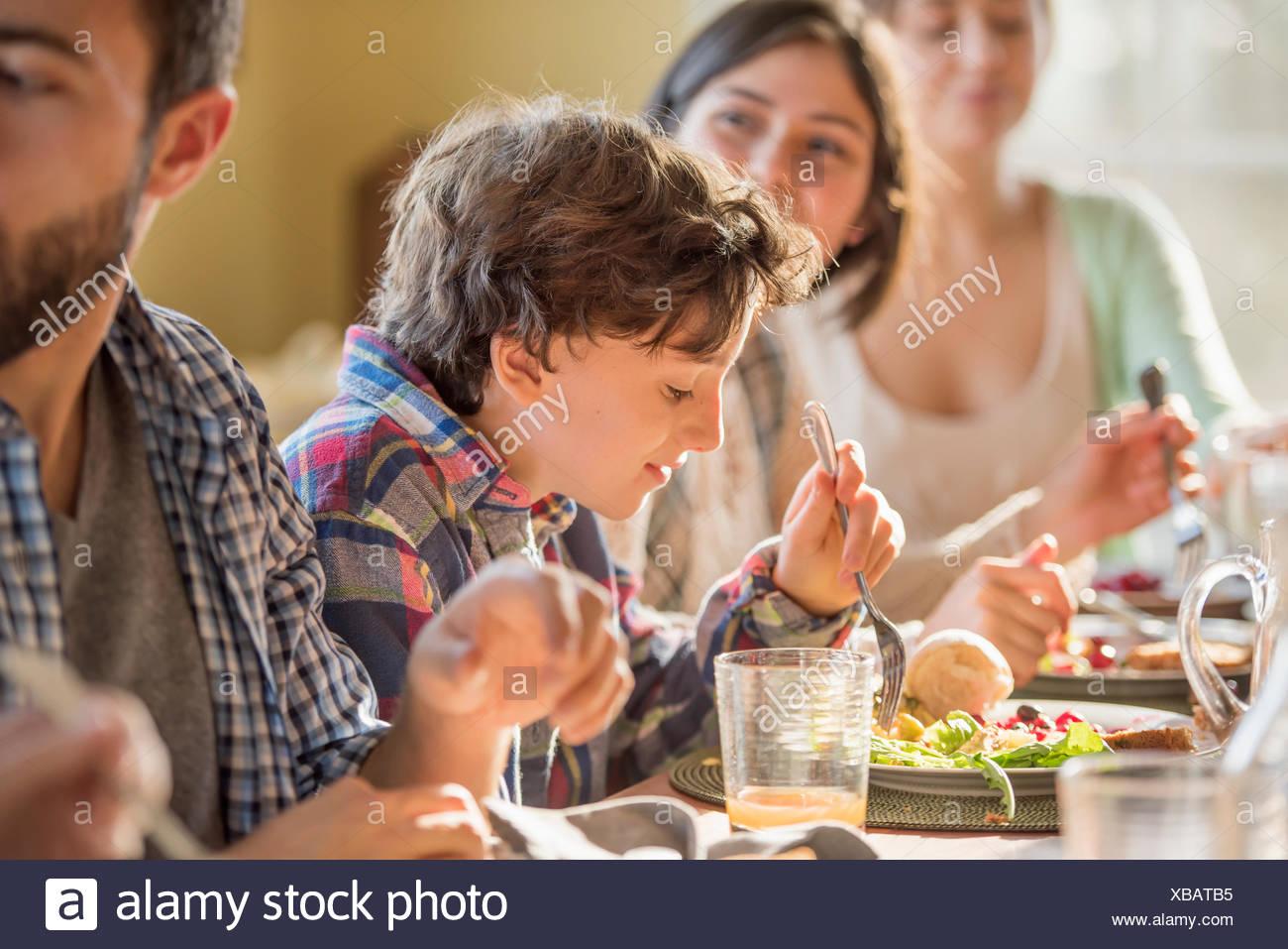 Un grupo de personas, adultos y niños, sentados alrededor de una mesa para comer. Imagen De Stock