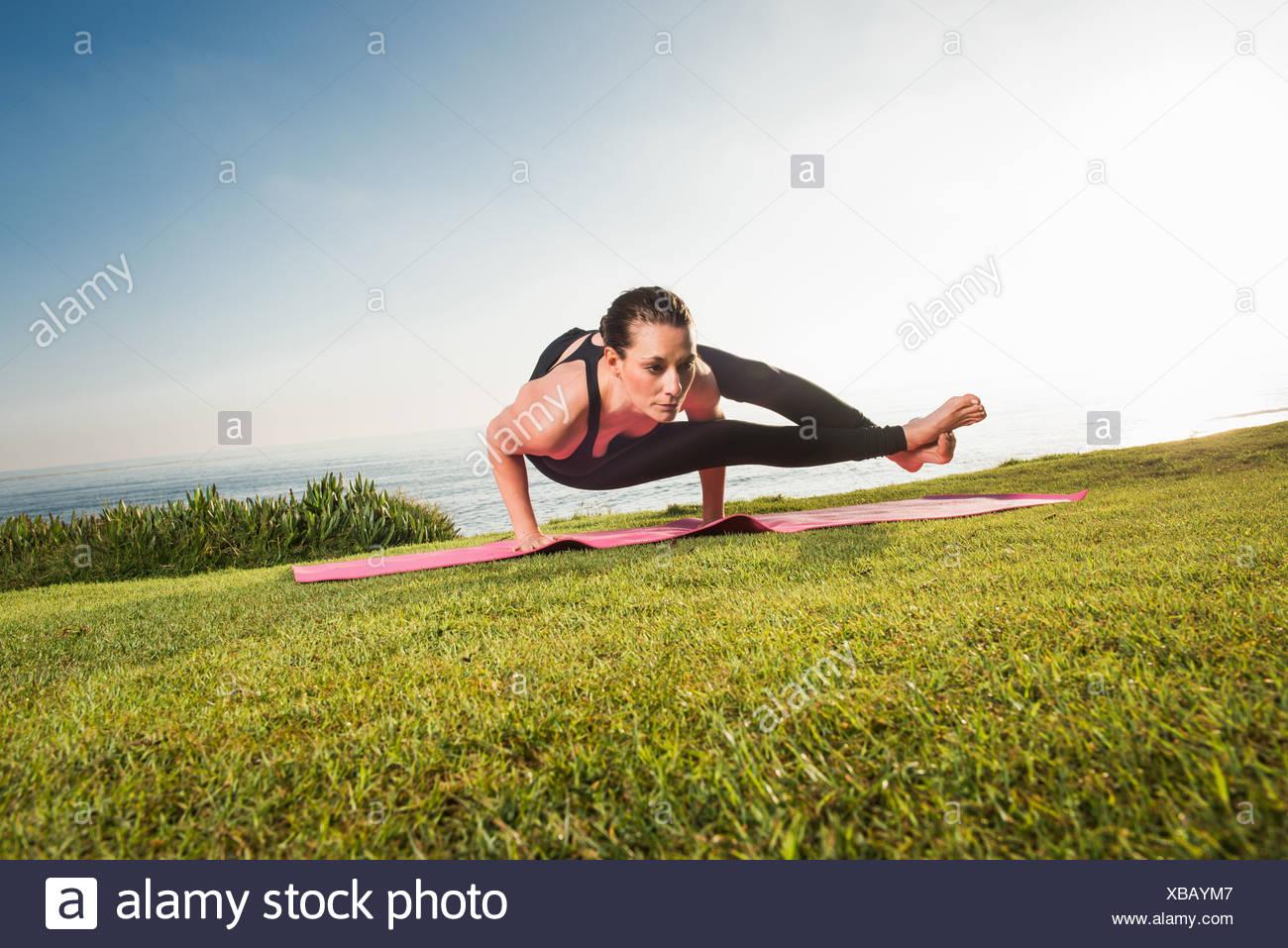 Las mujeres sobre un acantilado, en posición de yoga Imagen De Stock