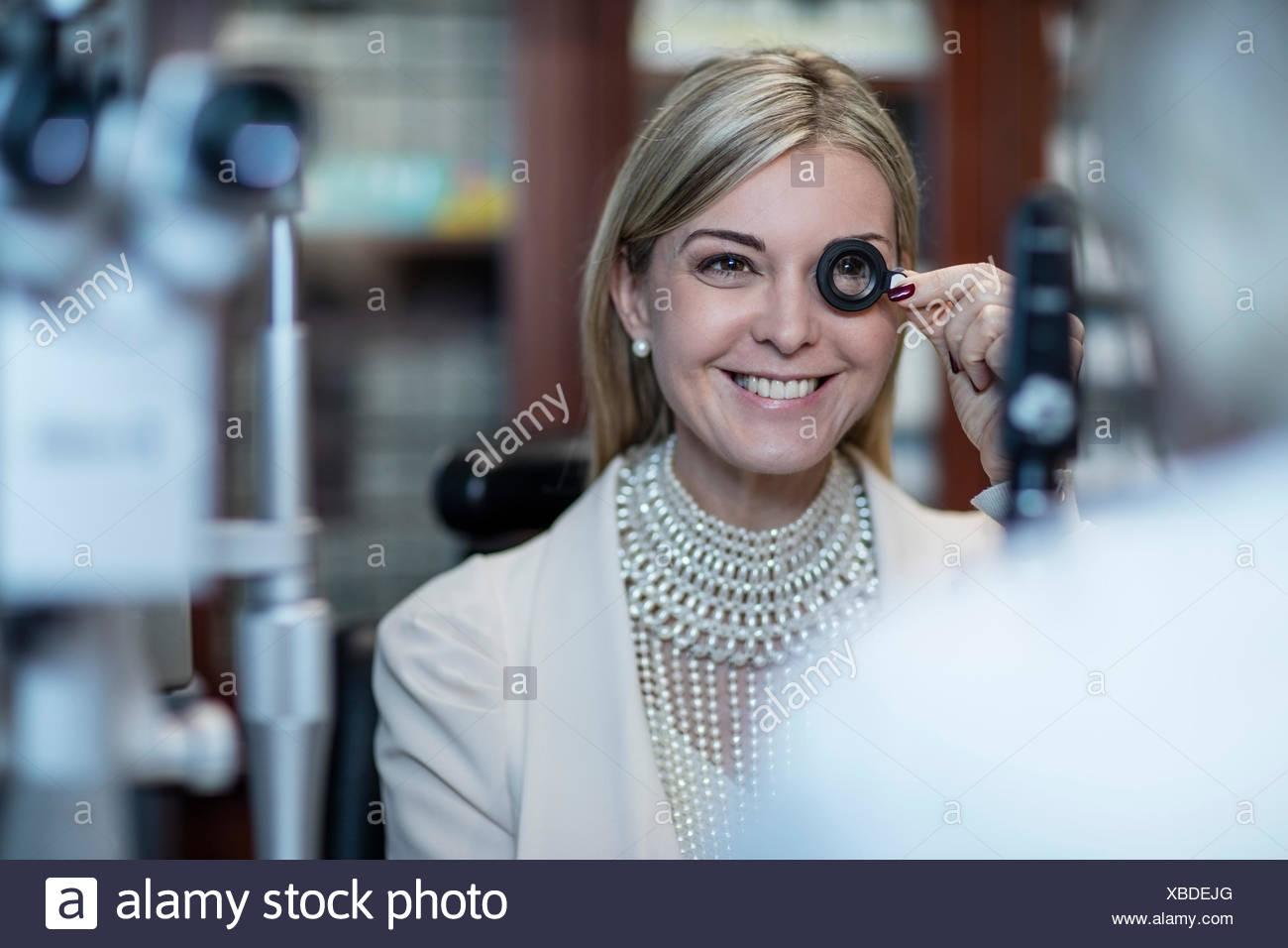 Paciente en el optometrista tratando diferentes lentes Foto de stock