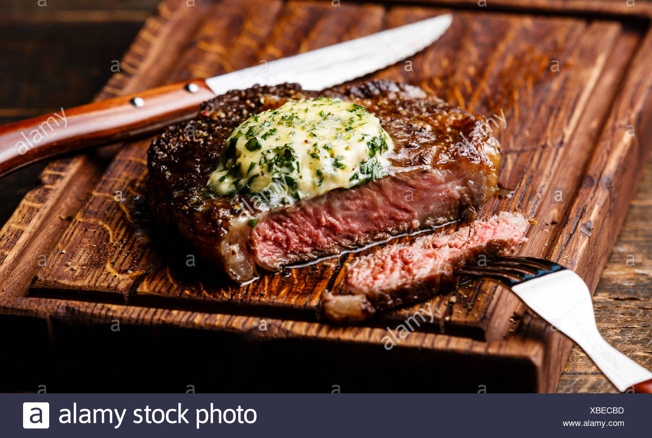 Medio raro el bistec a la parrilla chuletón con mantequilla de finas hierbas sobre placa de corte serving size Imagen De Stock
