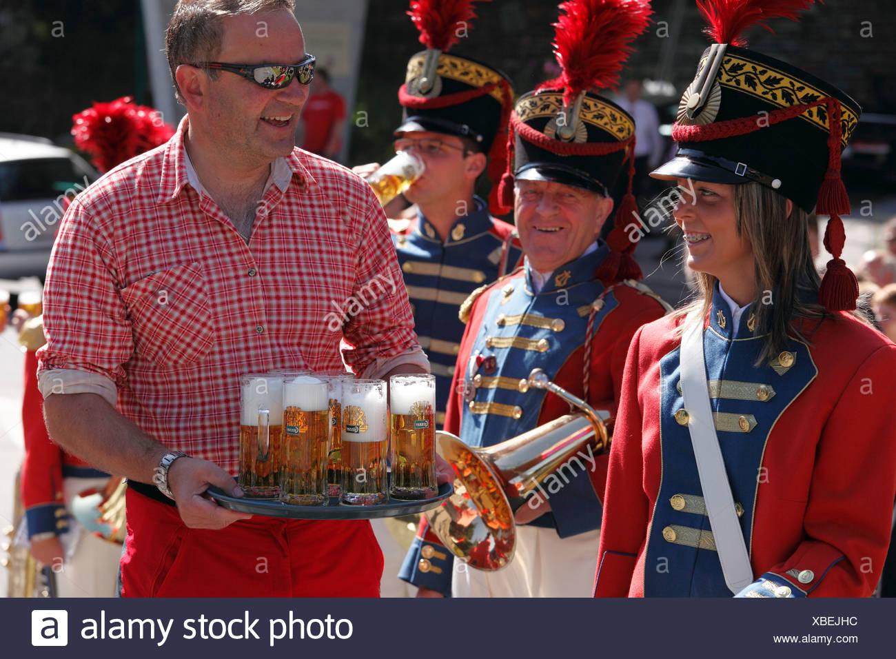 Dueño servir cerveza para el grupo de música local de San Miguel, en el Desfile de Sansón, Katschberg, Lungau, estado de Salzburgo, Salzb Foto de stock