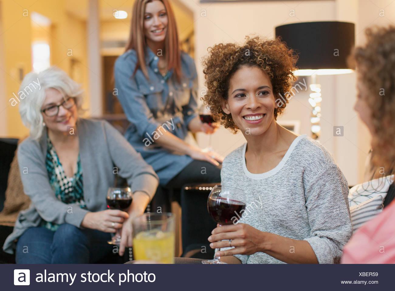 Amigos disfrutando del vino y conversación en casa. Imagen De Stock