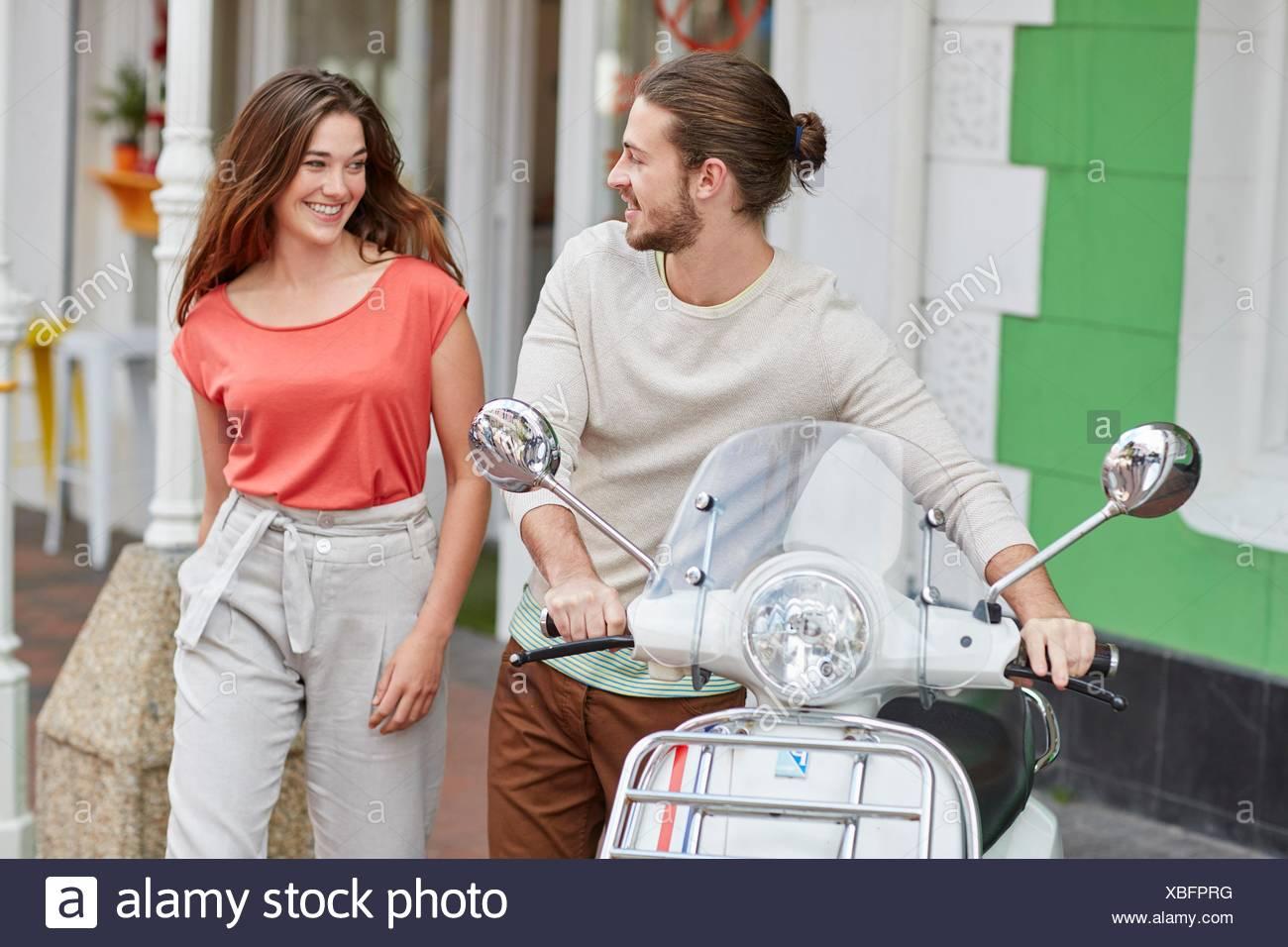 Modelo liberado. Pareja joven fuera de la cafetería, hombre sujetando ciclomotor. Imagen De Stock