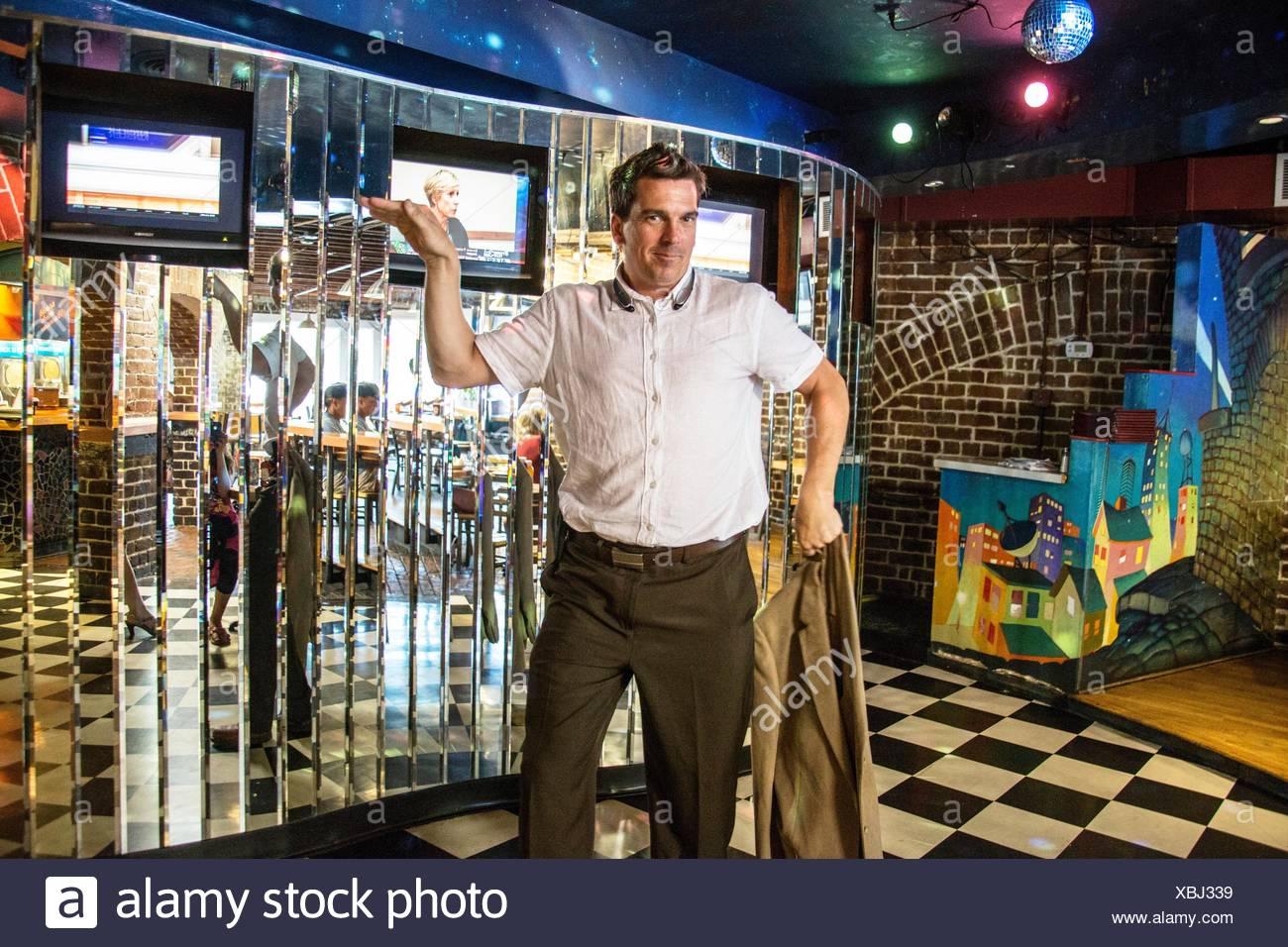 Cabello oscuro caucásica guapo padre en sus 30's 40's 50's con una camisa blanca de manga corta bailando en la discoteca, y la celebración de su chaqueta en sus manos en un Imagen De Stock