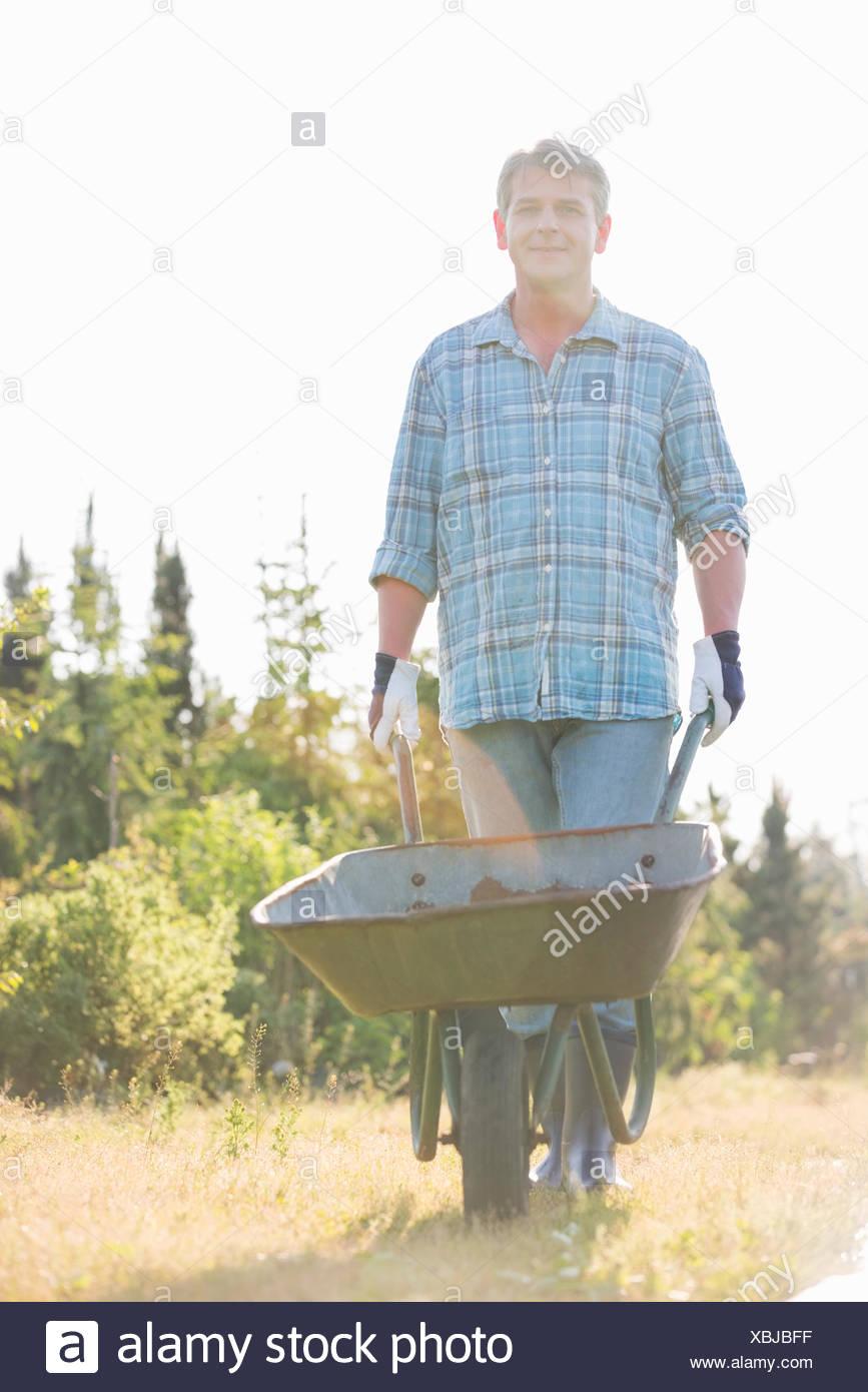 Retrato del jardinero macho empujando la carretilla de mano en el jardín Imagen De Stock