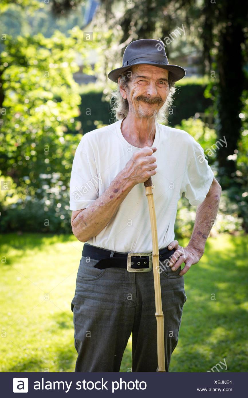 Retrato del hombre senior con sombrero y bigote de pie en el jardín Imagen  De Stock 8e17c8aaaee