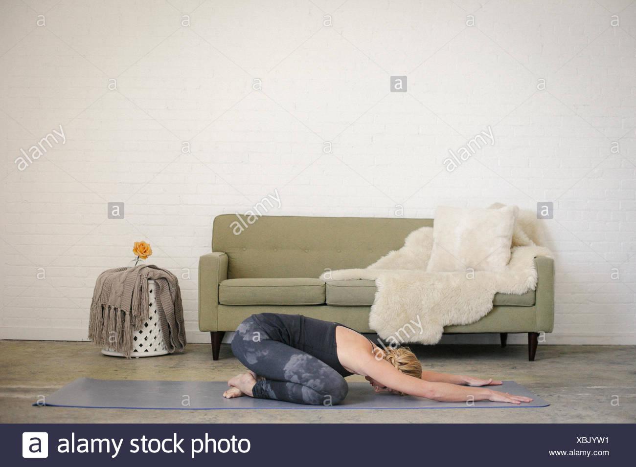 Una mujer rubia, arrodillado sobre una estera del yoga en una habitación, hacer yoga, su brazo estirado en frente de ella. Imagen De Stock