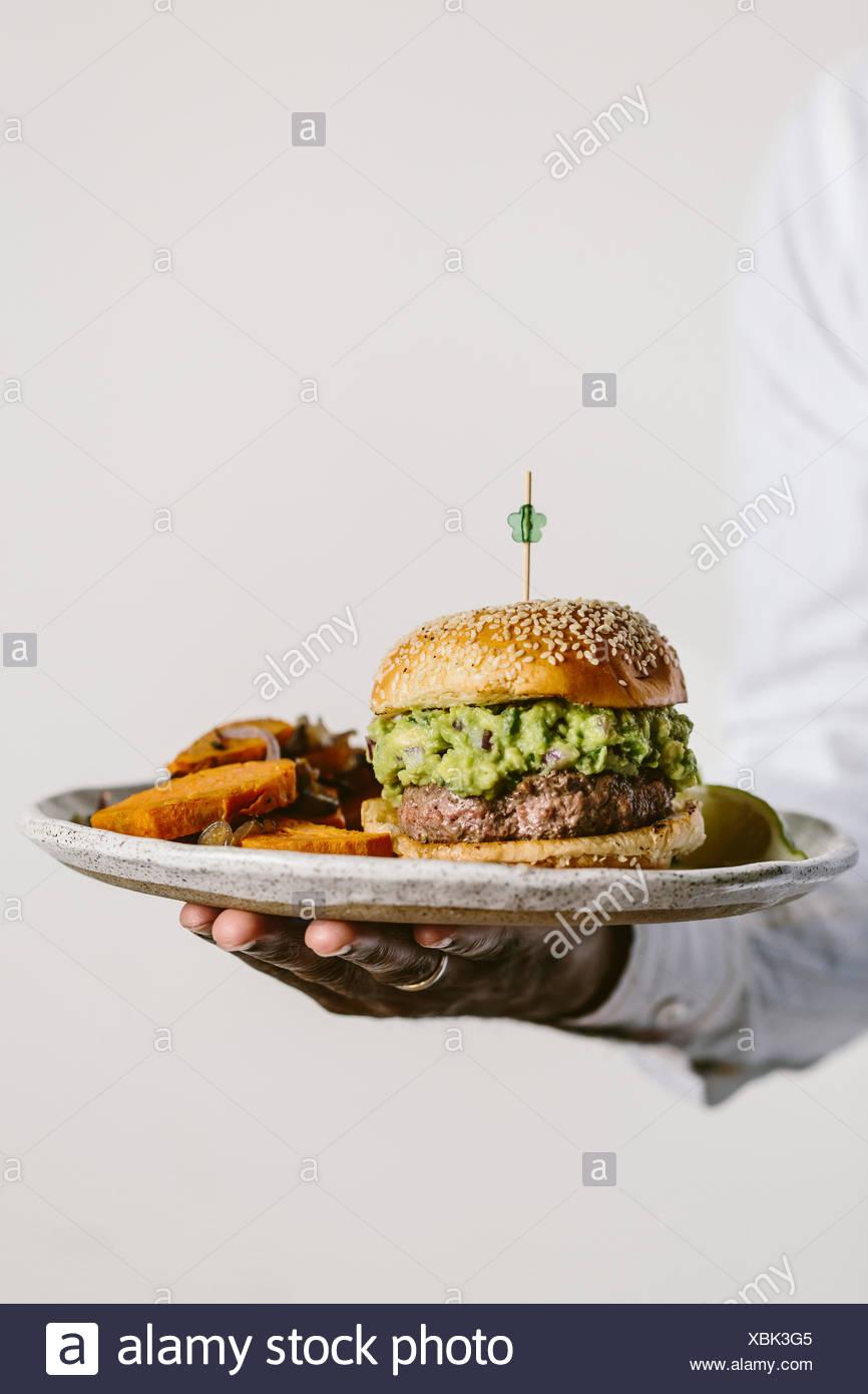 Un hombre es fotografiado desde la vista frontal sujetando un plato de guacamole hamburguesa y patatas fritas de camote. Imagen De Stock