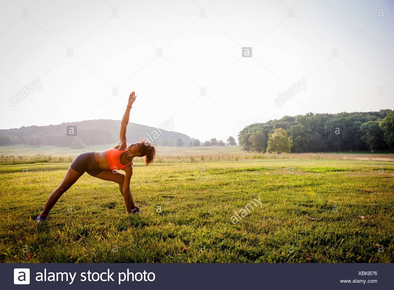 Mujer joven practicando yoga en parque rural Foto de stock