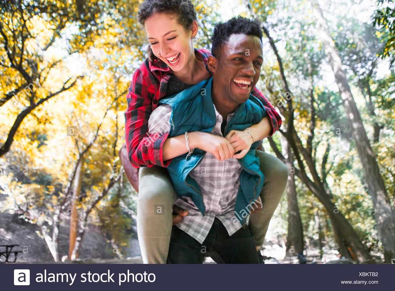 Mujer joven excursionista llegar piggy back del novio en el bosque, Arcadia, California, EE.UU. Imagen De Stock