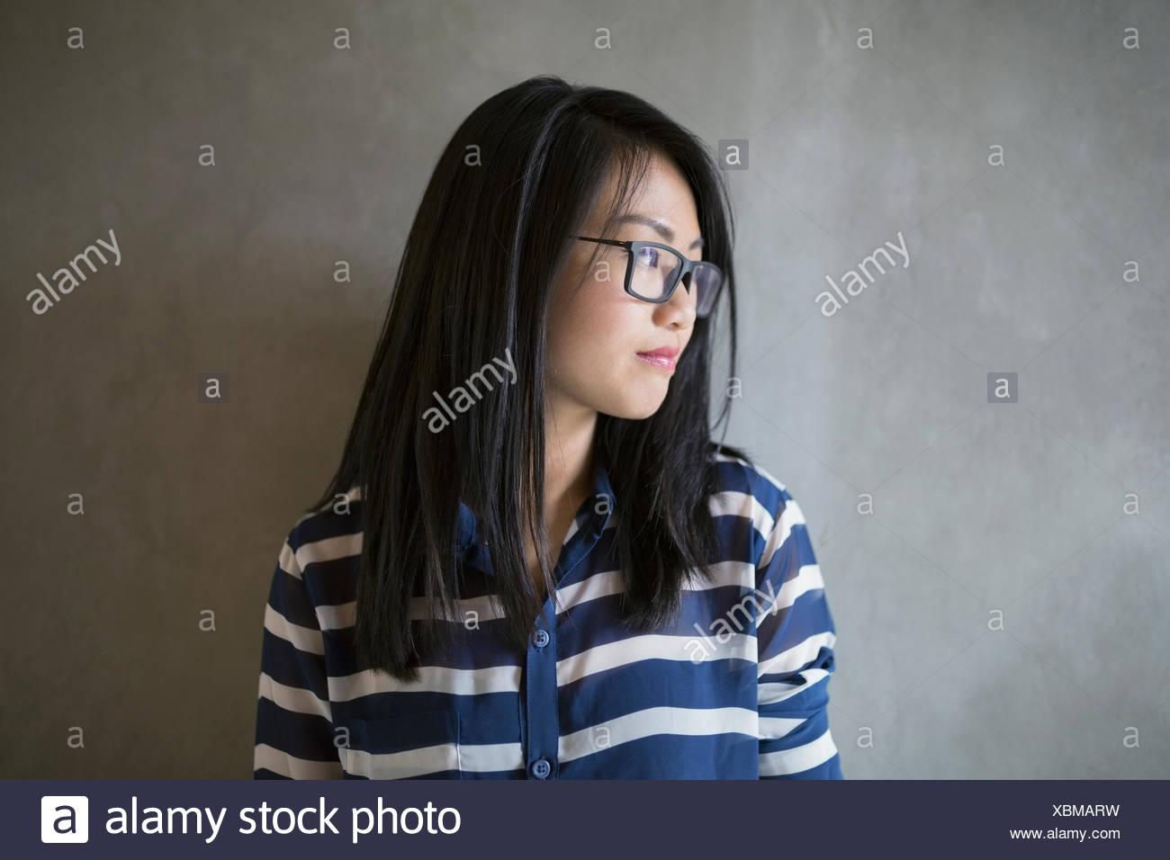 ded5a5e53c Pensativo empresaria cabello negro y anteojos mirando lejos Foto ...