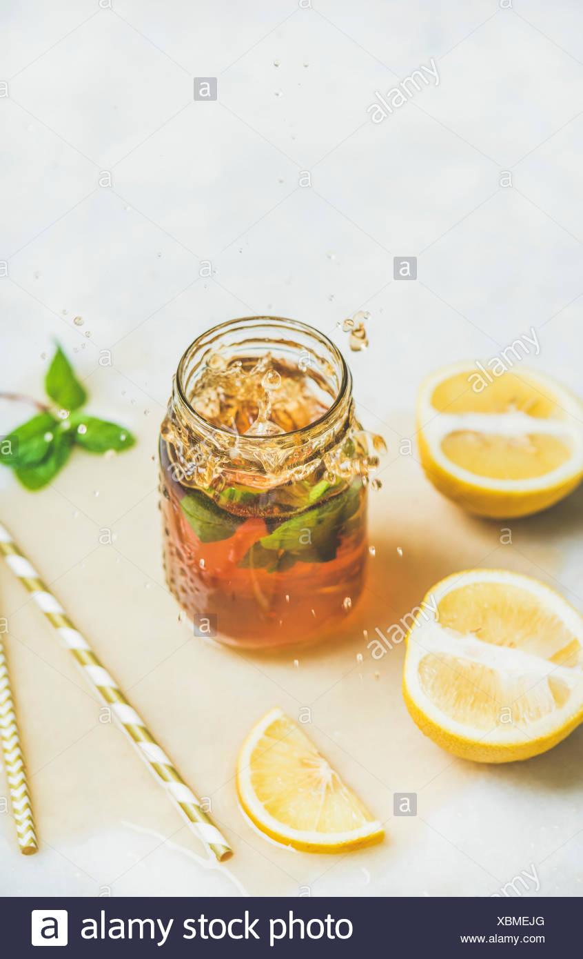 Verano frío helado de té con menta fresca, de bergamota y limón en tarro de vidrio con las salpicaduras sobre la mesa de luz de fondo, copia el espacio. Alimentos en concepto de movimiento Foto de stock