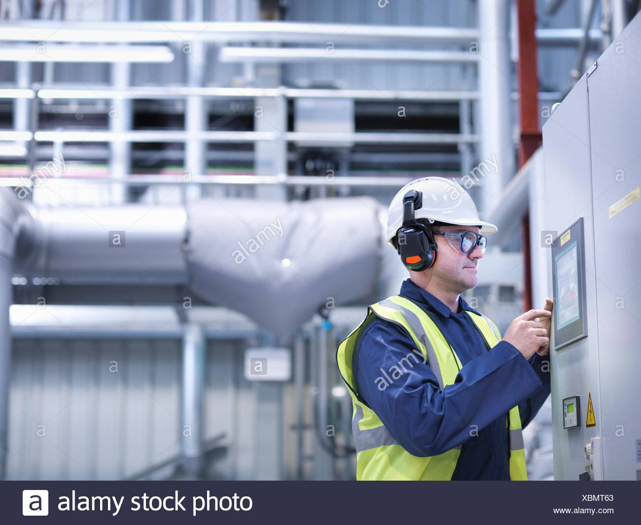 Trabajador por medio de controles con pantalla táctil en la central eléctrica alimentada con gas Imagen De Stock