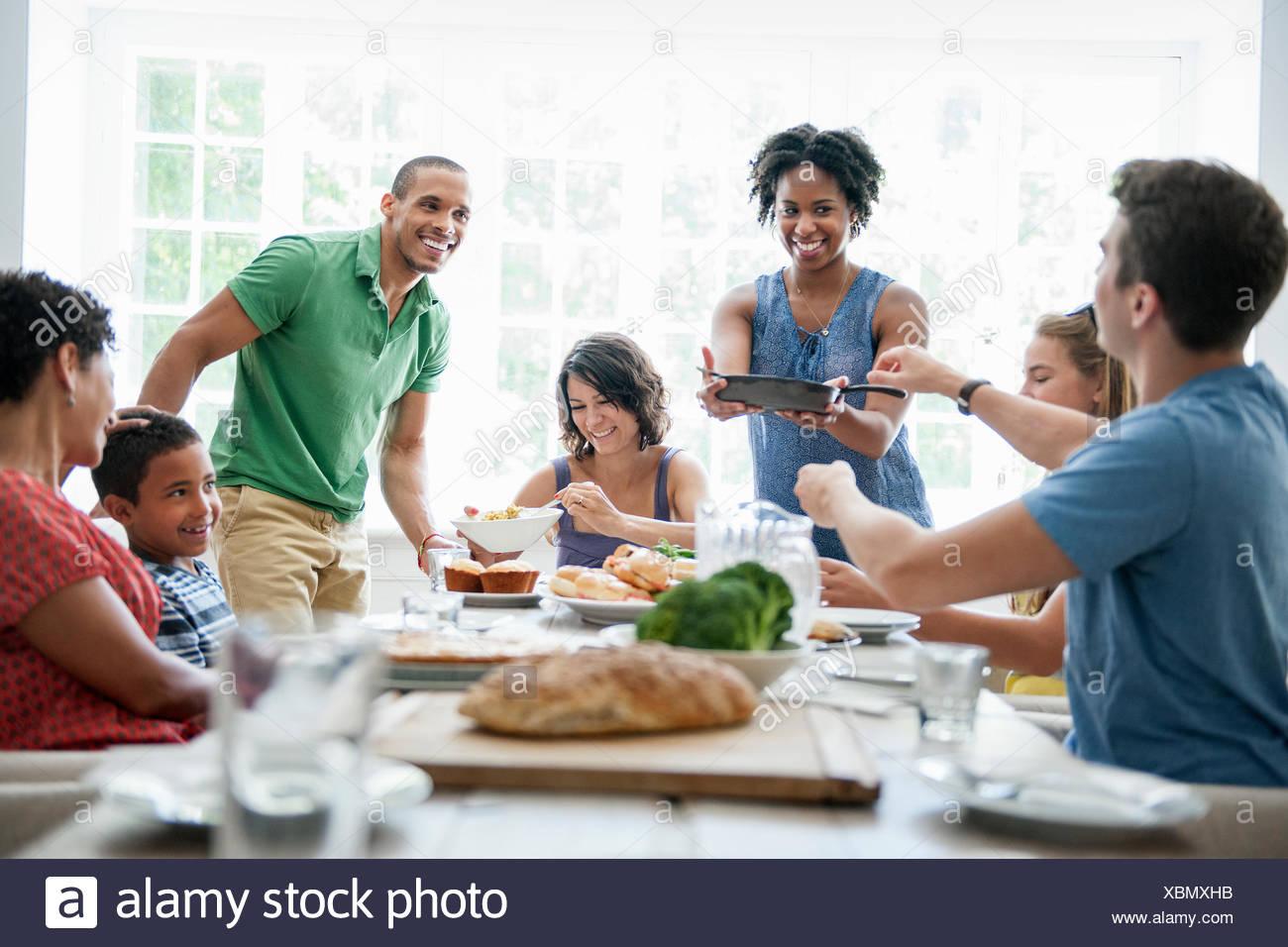Una reunión familiar para una comida. Adultos y niños alrededor de una mesa. Imagen De Stock