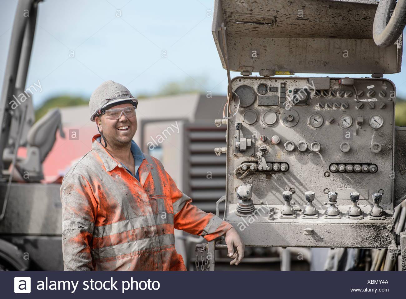 Perforación trabajador en sombrero duro y ropa de trabajo, sonriente Imagen De Stock