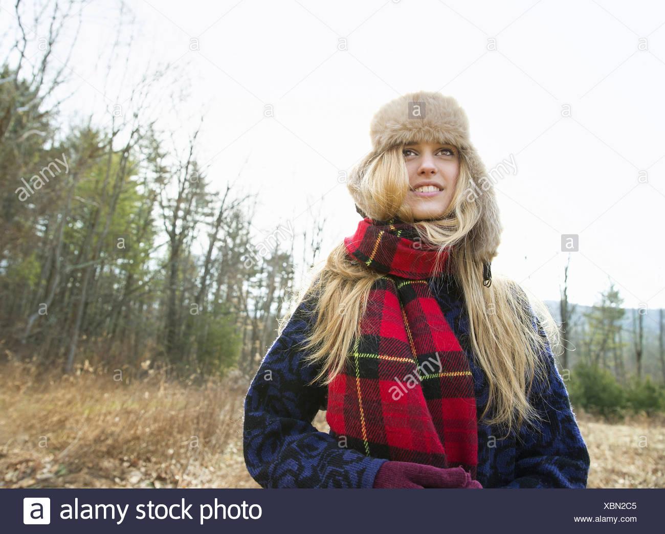 Una mujer en un ambiente cálido y peludo y un sombrero rojo grande tartan bufandas afuera en el invierno Imagen De Stock