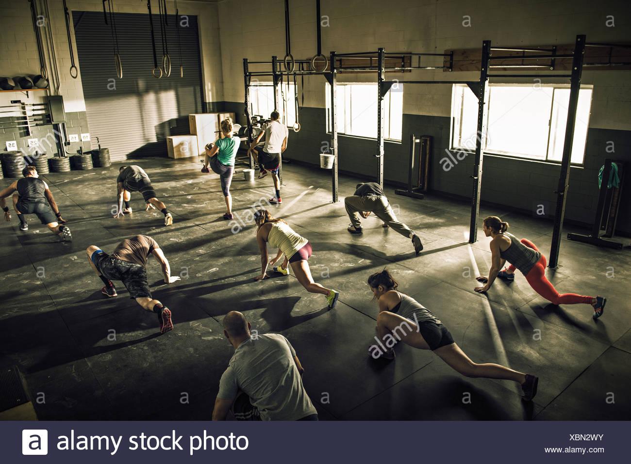 Formación de la clase de gimnasia y estiramiento junto en el gimnasio Imagen De Stock