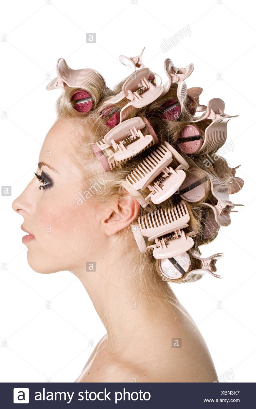Hermosa joven está teniendo rizadores de pelo en su cabeza Imagen De Stock